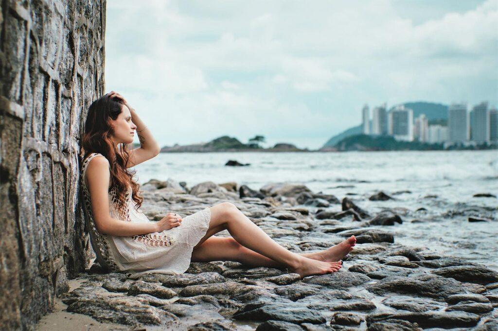 kobieta w ubraniu myśli przy morzu